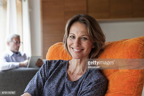 smiling woman relaxing in armchair with husband in background - baby boomer stock-fotos und bilder