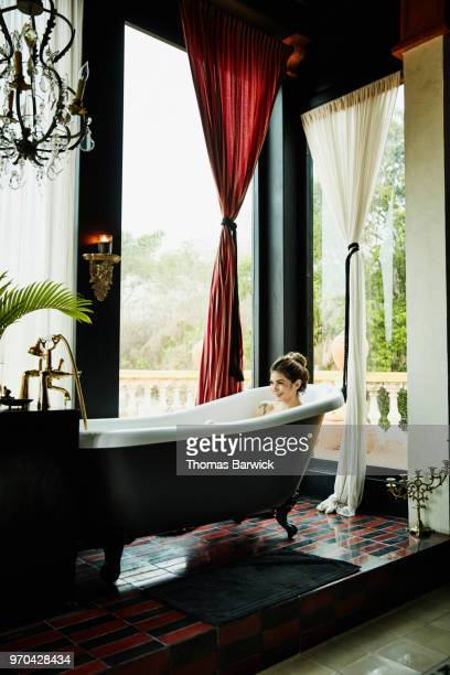 Smiling woman relaxing in bathtub