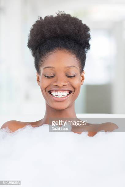 Smiling woman relaxing in bubble bath