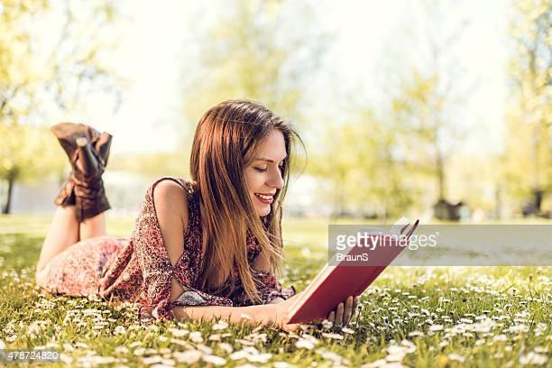 Mujer sonriente descansando en la hierba leyendo un libro.