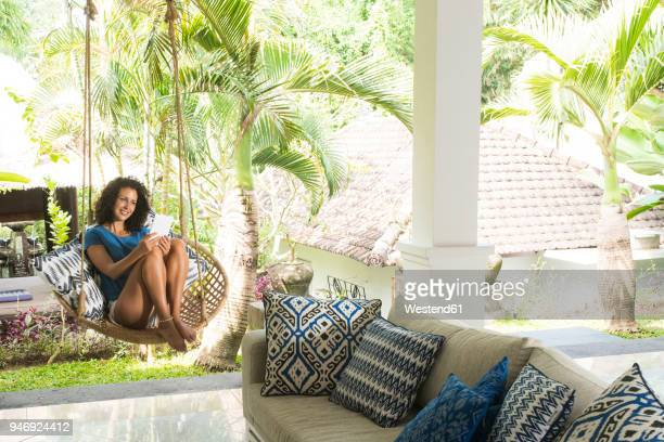 smiling woman relaxing in hanging chair holding e-reader - accessibility stock pictures, royalty-free photos & images