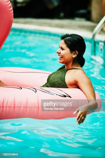 smiling woman relaxing in inflatable pool toy - inflatable stock pictures, royalty-free photos & images