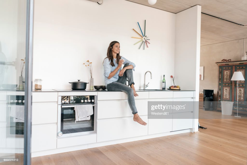 Smiling woman relaxing in kitchen at home : Stock Photo