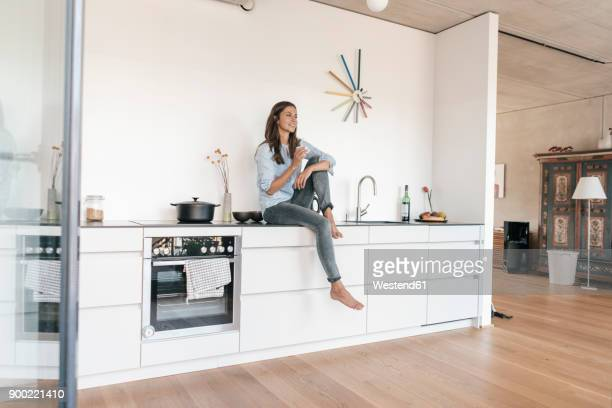 Smiling woman relaxing in kitchen at home