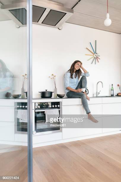 smiling woman relaxing in kitchen at home - cuisine non professionnelle photos et images de collection