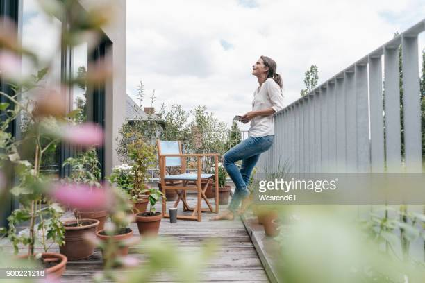 smiling woman relaxing on balcony holding tablet - focus on background stock pictures, royalty-free photos & images