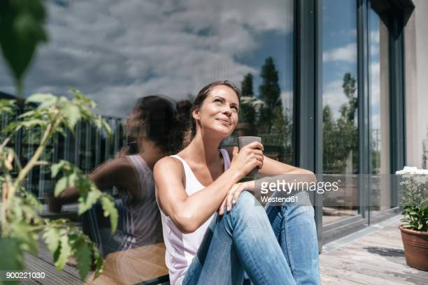 smiling woman relaxing on balcony - sunlight stock-fotos und bilder