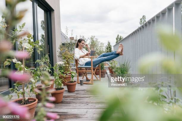 Smiling woman relaxing on balcony using tablet