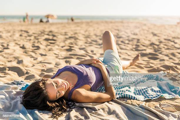 smiling woman relaxing on beach towel - 30 39 years stock pictures, royalty-free photos & images