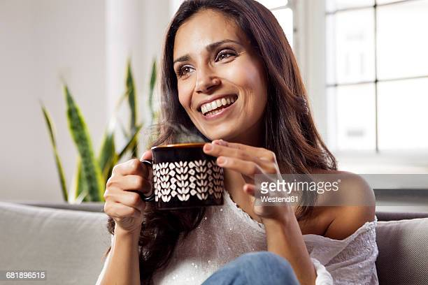 Smiling woman relaxing on couch holding a mug