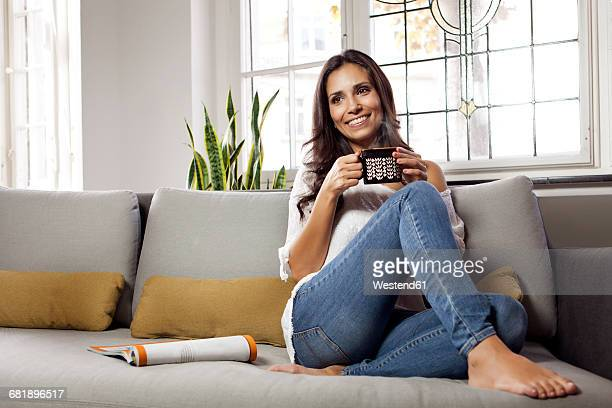 smiling woman relaxing on couch holding a mug - mixed magazine stock photos and pictures