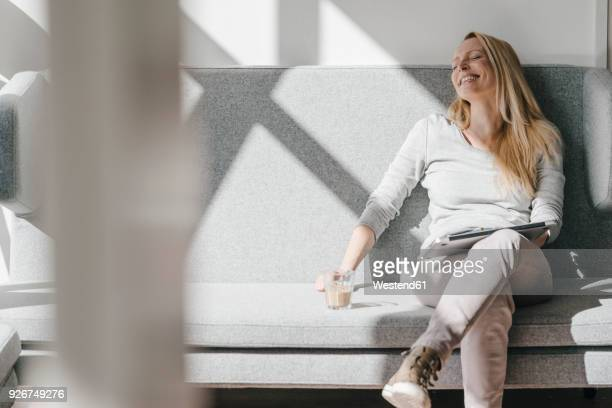 smiling woman relaxing on couch with laptop - sofa stock-fotos und bilder