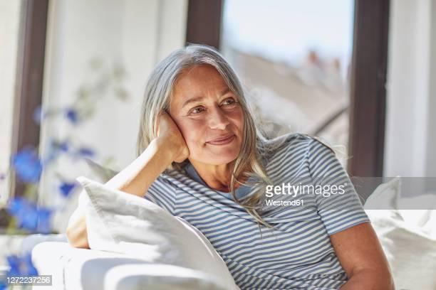 smiling woman relaxing on sofa in living room - graues haar stock-fotos und bilder