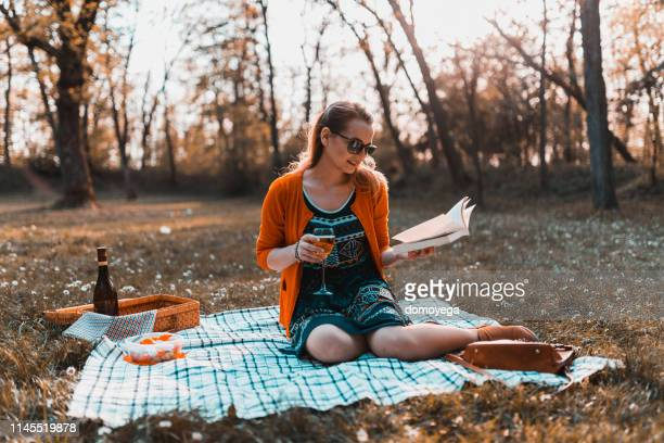smiling woman relaxing with a book during a picnic in park - solo ragazze foto e immagini stock