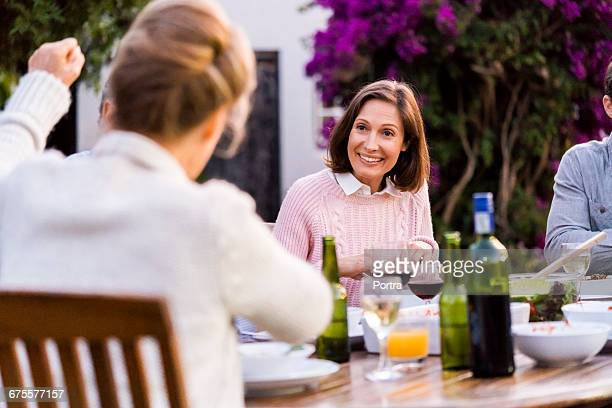 Smiling woman relaxing with family at table