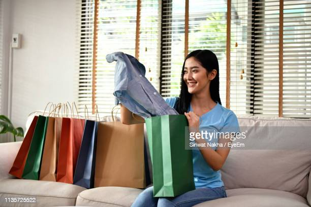 smiling woman removing dress from shopping bags while sitting on sofa - remove clothes from stock pictures, royalty-free photos & images