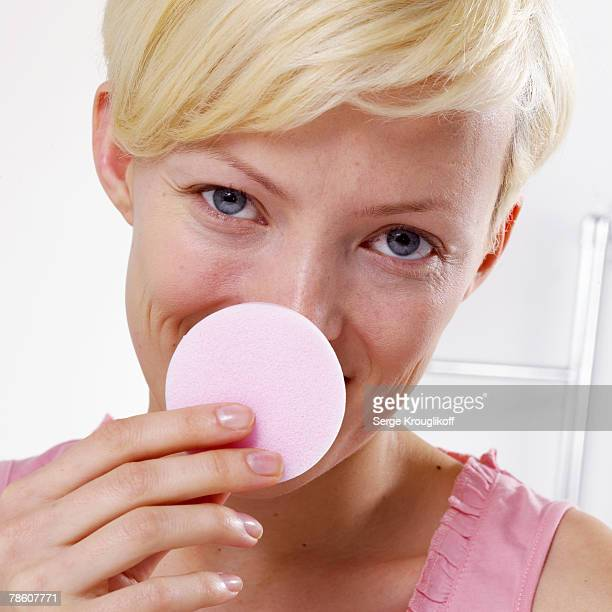 Smiling woman removing makeup with cotton pad