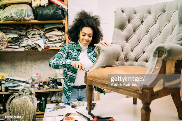 Smiling woman renovating old furnitures in upholstery studio