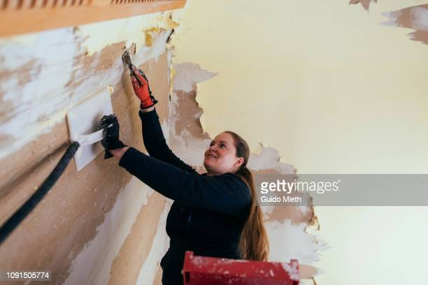Smiling woman renovating own property.