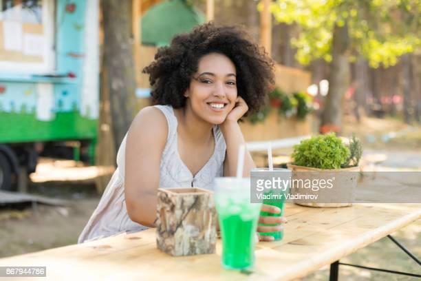 Femme souriante, se reposer et boire un cocktail