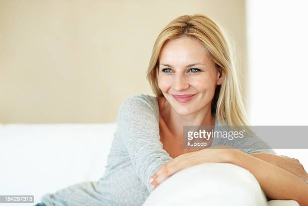 Smiling woman resting on couch
