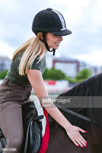 smiling woman riding a horse - tame stock photos and pictures