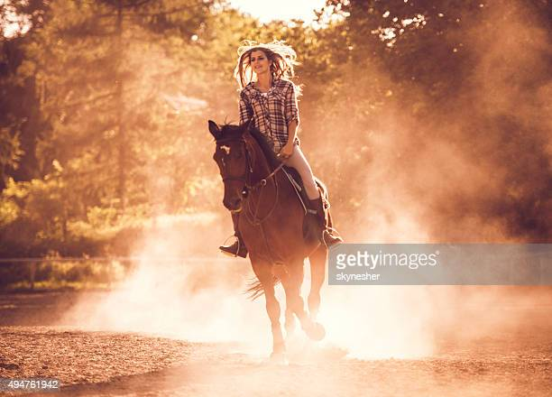 Smiling woman riding a stallion at sunset.