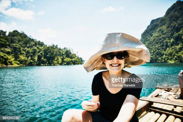 Smiling woman riding on bamboo raft in Khao Sok National Park Thailand