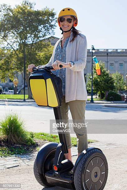 Smiling woman riding segway in city, Philadelphia, Pennsylvania, USA