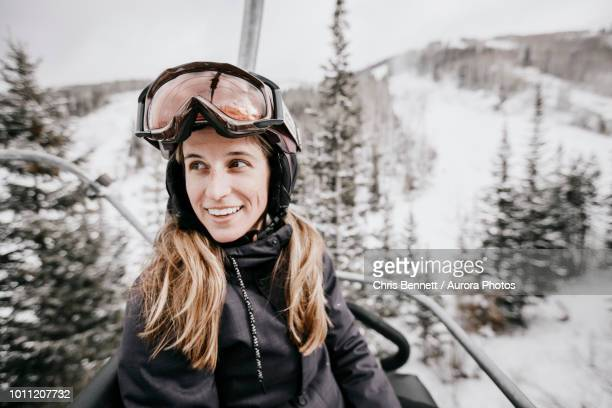 smiling woman riding ski lift - ski lift stock pictures, royalty-free photos & images