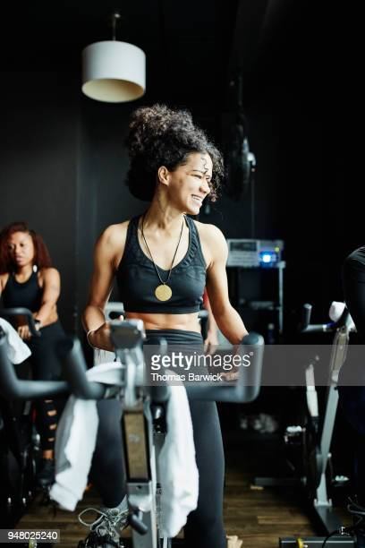 Smiling woman riding stationary bike during fitness class in studio
