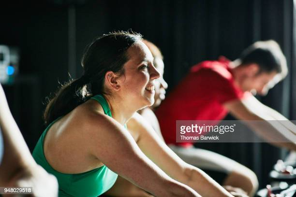 Smiling woman riding stationary bike during fitness class with friends in cycling studio