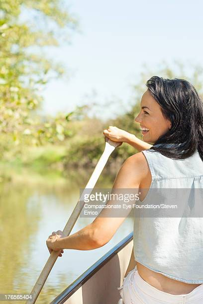 Smiling woman rowing canoe on river