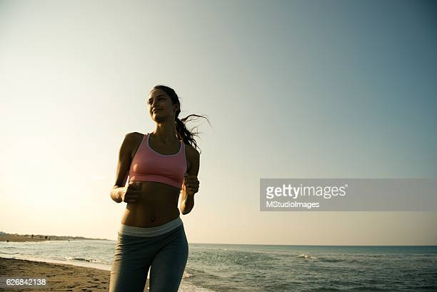 Smiling woman running at the beach.