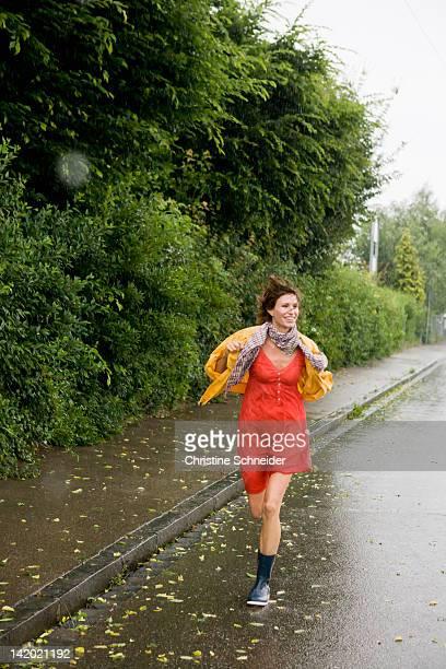 smiling woman running in rain - gummistiefel frau stock-fotos und bilder