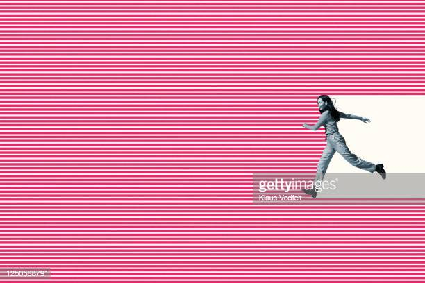 smiling woman running on pink striped pattern - positive emotion stock pictures, royalty-free photos & images