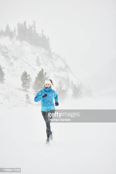 smiling woman running on road during winter snow storm - forward athlete stock pictures, royalty-free photos & images