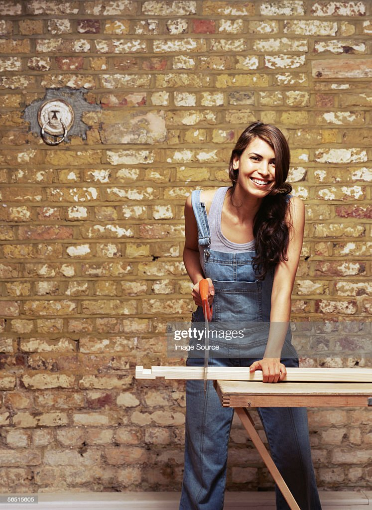 Smiling woman sawing wood : Stock Photo