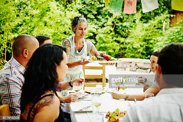 Smiling woman serving entree to friends