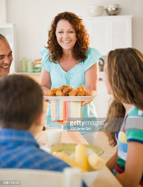 smiling woman serving family dinner - fried chicken stock photos and pictures