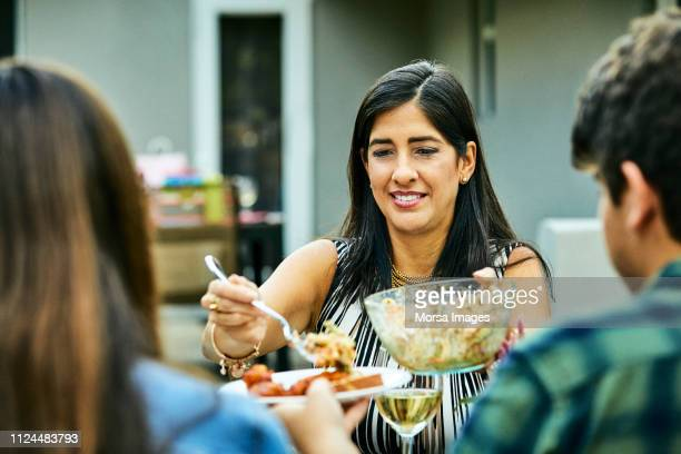 smiling woman serving food to teenagers at table - celebration fl stock pictures, royalty-free photos & images