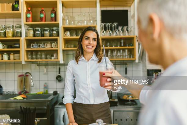 Smiling Woman serving smoothie to customer
