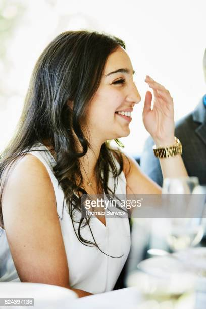 Smiling woman sharing a meal with friends in restaurant