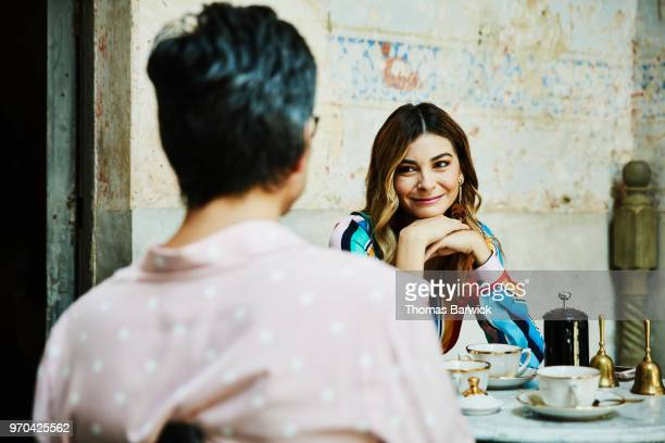 Smiling woman sharing coffee with husband while seated at outdoor cafe