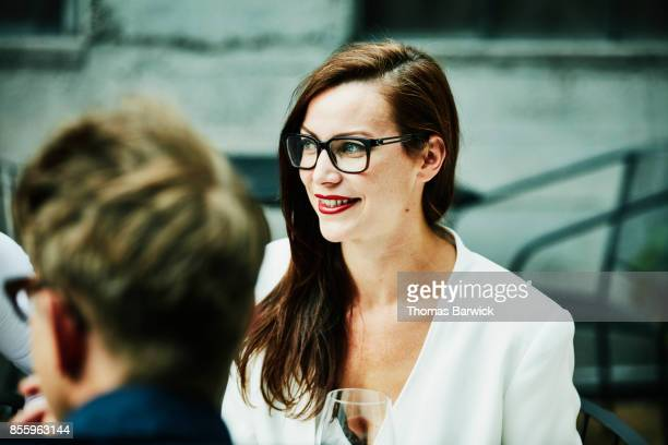 Smiling woman sharing dinner with friends on restaurant patio on summer evening