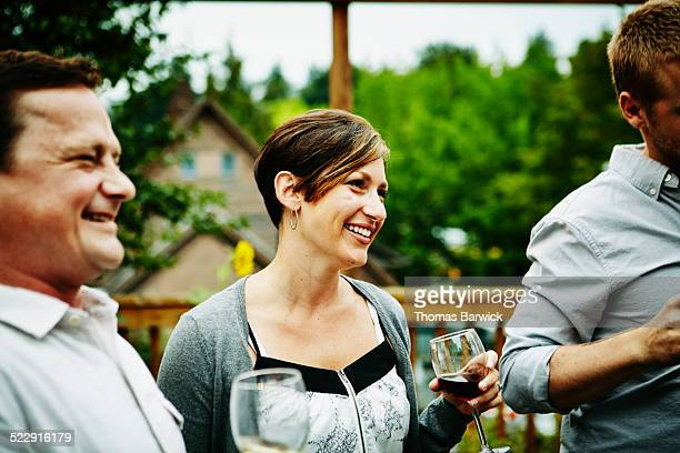 Smiling woman sharing wine with friends on deck