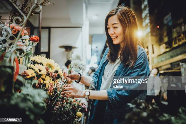 smiling woman shopping for fresh flowers in flower shop - florist stock pictures, royalty-free photos & images