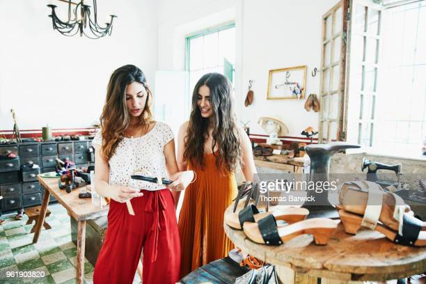 smiling woman shopping with friend in handmade shoe boutique - red pants stock pictures, royalty-free photos & images