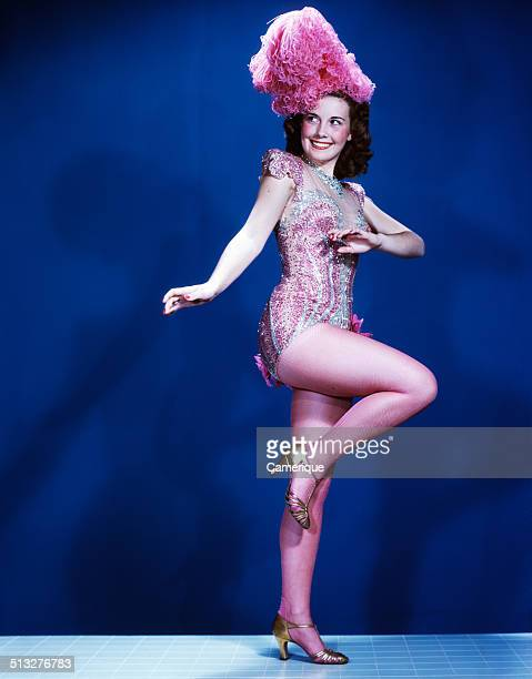 Smiling woman showgirl dancer performer wearing pink burlesque costume with feather headpiece Los Angeles California 1949