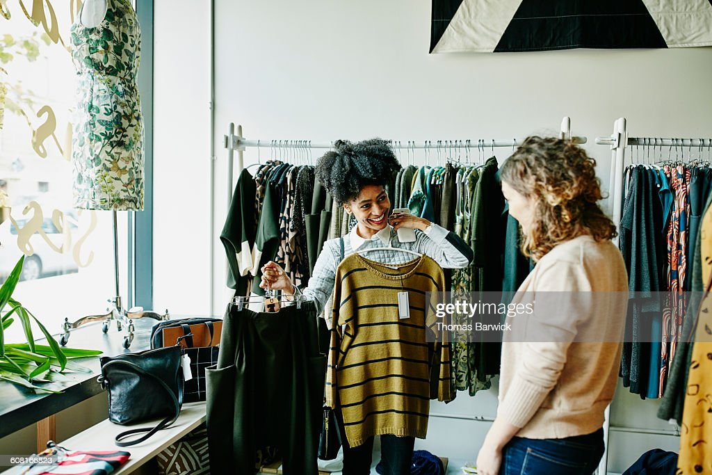Smiling woman showing shop owner clothing options : Stock Photo